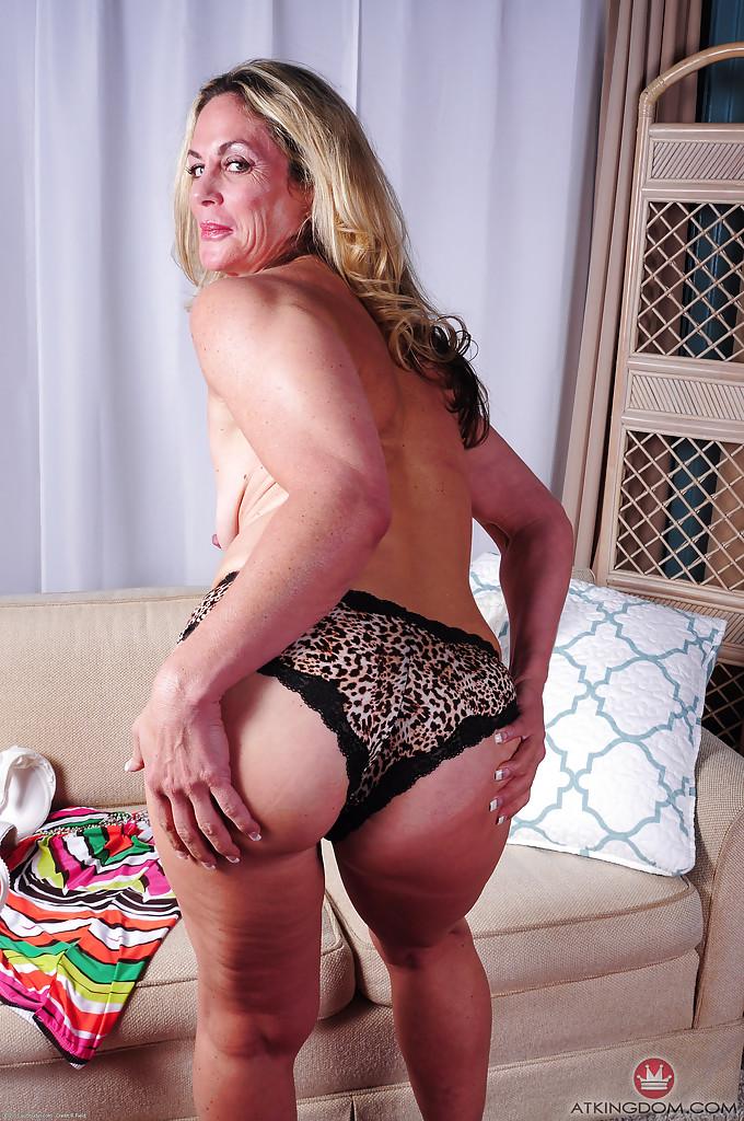 Взрослая модель со свелыми волосами Sydney сняв трусы лежит нагая на диване